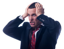 Angry young businessman holding his head Royalty Free Stock Image
