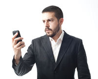 Angry young businessman looking mobile phone. Stock Images