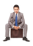 Angry young businessman sitting on a suitcase Royalty Free Stock Photos