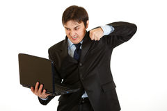 Angry young businessman trying to hit laptop Royalty Free Stock Images