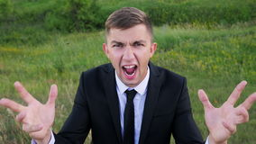 Angry young businessman yelling at camera stock footage