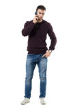 Angry young casual man talking on the phone looking at camera. Royalty Free Stock Photos