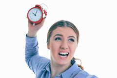Angry young Caucasian woman throwing an alarm clock isolated in white background. Angry furious young Caucasian woman throwing an alarm clock isolated in white Stock Photos