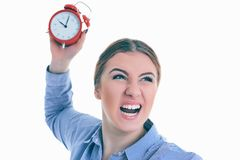 Angry young Caucasian woman throwing an alarm clock isolated in white background. Angry furious young Caucasian woman throwing an alarm clock isolated in white Royalty Free Stock Photography