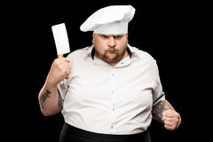 Angry young chef in hat holding meat knife and shaking fist. Isolated on black Stock Photos