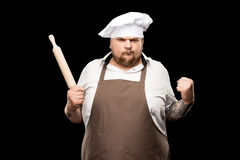 Angry young chef holding rolling pin and shaking fist. Isolated on black Royalty Free Stock Photo