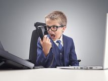 Angry young businessman boy shouting into a phone royalty free stock photo