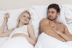 Angry young couple looking at each other in bed Royalty Free Stock Photos