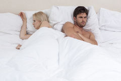 Angry young couple lying in bed Royalty Free Stock Photo