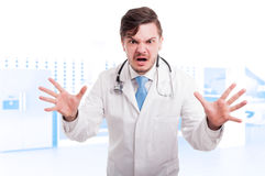 Angry young doctor showing rage and screaming Royalty Free Stock Photo