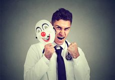 Angry doctor taking off smiling mask royalty free stock photo