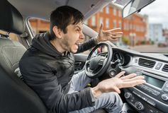 Angry young driver is driving a car and shouting.  Royalty Free Stock Image