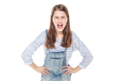 Angry young fashion girl in jeans overalls screaming isolated Royalty Free Stock Photo