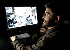Angry young gamer playing videogame. On computer in dark room Royalty Free Stock Images