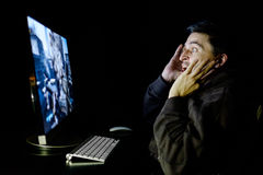 Angry young gamer playing videogame. On computer in dark room Royalty Free Stock Image