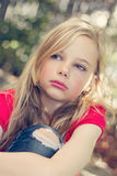 Angry young girl. A young girl with an angry expression sitting in the garden Royalty Free Stock Photography