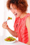 Angry young girl eating tasty salad Royalty Free Stock Image