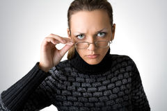Angry young girl. With glasses on gray background royalty free stock photography