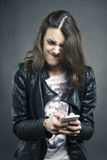 Angry young girl looking at phone with disgusting emotion Stock Photo