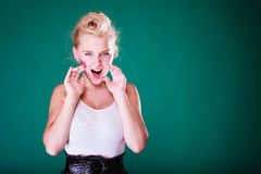 Angry young girl screaming, hands close to mouth. Yelling gestures concept. Angry pin up girl screaming with hands close to mouth. Studio shot on green Royalty Free Stock Photo
