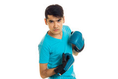 Angry young guy practicing boxing in blue gloves isolated on white background Stock Image