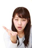 Angry young Japanese woman requests something. Studio shot of young Japanese woman on white background stock photos