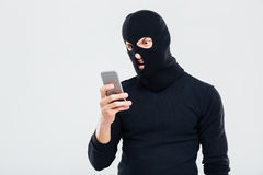 Angry young man in balaclava using cell phone Royalty Free Stock Photos