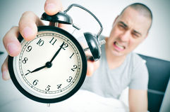Angry young man in bed holds his alarm clock Stock Image