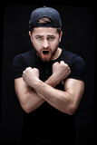 Angry young man in the black shirt and cap screaming on black background. Royalty Free Stock Images
