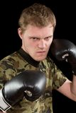 Angry young man in boxing gloves Royalty Free Stock Photography