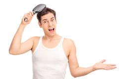 Angry young man brushing his hair Royalty Free Stock Photos