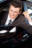 Angry young man clenching his fist, sitting in new car Stock Photos