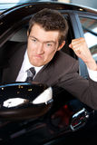 Angry young man clenching his fist, sitting in new car Stock Photo