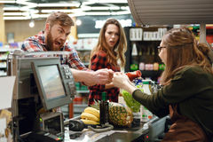 Angry young man doesn`t give the credit card to cashier. Image of angry young men standing in supermarket shop near cashier`s desk doesn`t give the credit card Stock Photo