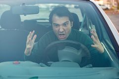 Angry young man driving a vehicle is expressing his road rage Stock Photos