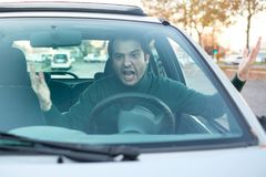 Angry young man driving a vehicle is expressing his road rage. Angry man driver pissed off by drivers in front of him and gesturing with hands Stock Photos
