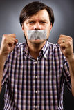 Angry  young man with duct tape over his mouth Royalty Free Stock Photos