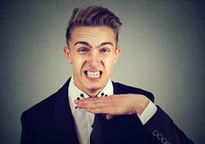 Angry young man gesturing with hand to stop talking, cut it out. Royalty Free Stock Photo