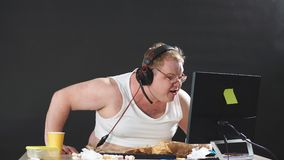 Angry young man in headset playing game at home.