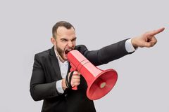 Angry young man hold red megaphone in hand nad screma into it. He points forward. Guy is mad. Isolated on white royalty free stock images