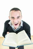Angry young man holding a book tired of reading Stock Photo