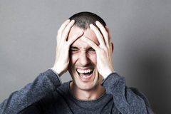 Angry young man holding his head, screaming his burnout. Portrait of an angry young man holding his head, screaming his burnout, expressing his frustration, rage Royalty Free Stock Photo