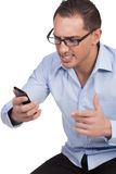 Angry young man looking at his mobile phone. Angry young man wearing eyeglasses looking at his mobile phone Royalty Free Stock Photo