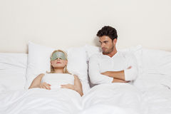 Angry young man looking at woman sleeping in bed Stock Photo