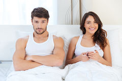 Angry young man lying on the bed with a woman Royalty Free Stock Photography