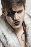 Angry young man with painted face wearing fur coat against gray background Royalty Free Stock Photos