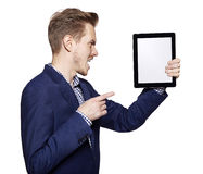 Angry young man pointing at tablet PC Stock Image