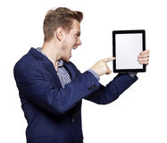 Angry young man pointing at tablet PC Royalty Free Stock Image