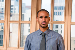 Angry Young Man Scowling. A well dressed, young African American male standing in front of a window with office buildings in the background scowls in anger Stock Image