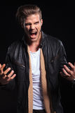 Angry young man screaming and gesturing. On a black background Stock Images